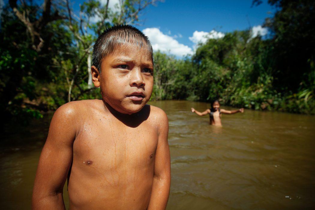 Crianças brincam num dos rios próximos ao tekoha Guyraroka. Ao lado da pequena faixa de mato, a imensidão de milho e cana voltam a dominar a paisagem. Foto: Tiago Miotto/Cimi
